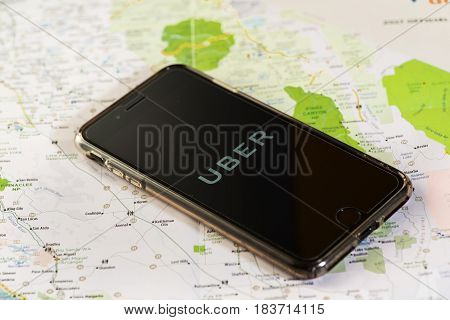Chicago,IL,USA,Feb-12,2017,Smartphone with an Uber application on the screen and a map  (for editorial use only)