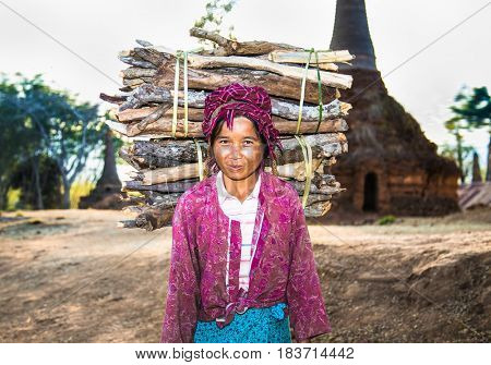 INLE, MYANMAR - MARC 4, 2017: Burmese woman carrying a bundle of heavy wood wearing traditional clothing on March  4, 2017, in Indein village , Myanmar. ( Burma)