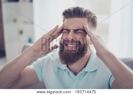 Handsome Young Guy Is Suffering From Strong Headache. He Is Holding His Head With Hands. Man Is Alon