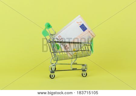 Fifty Euro In The Shopping Pushcart, Yellow Background