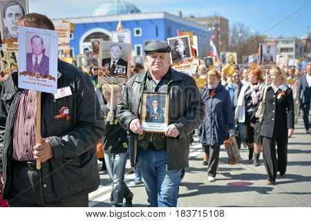 Yoshkar-Ola, Russia - May 8, 2015 A man with a photo in hand during the action immortal regiment, timed to the Victory Day on May 9, passing along the Leninsky prospect of the city of Yoshkar-Ola