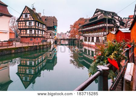 Traditional Alsatian half-timbered houses in Petite France with mirror reflections in the morning, Strasbourg, Alsace, France