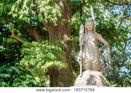 Unknown women mermaid sculpture on trees background in Milano city center park Shiny summer day
