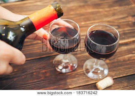 Female hand pouring red wine from bottle into two glasses