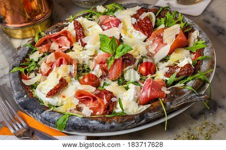 Black pizza with Parma ham parmesan cheese dried tomatoes rocket and basil.