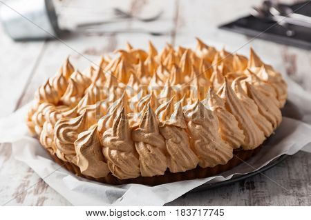A delicious meringue pie on a wooden table