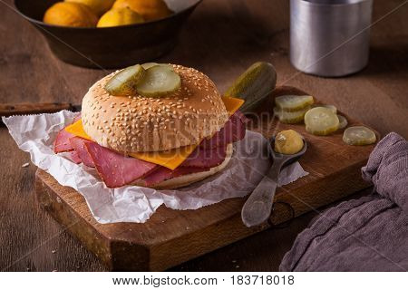 A delicious pastrami sandwich on a wooden cutting board in a rustic kitchen.