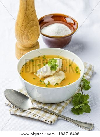 Fish soup with fresh coriander in a bowl.
