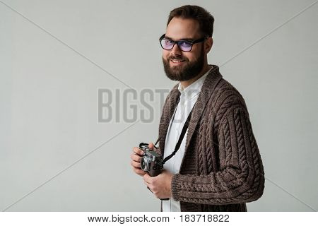 Portrait of positive hipster photographer with camera isolated in studio