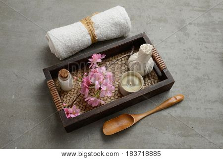 pink cherry flowers with candle, herbal ball ,oil in basket and towel on gray background