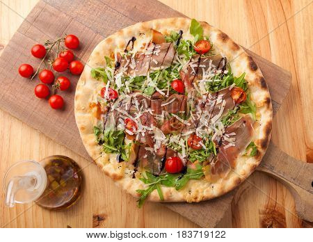 Pizza with dried ham rocket leaves tomato and Parmesan cheese on a cutting board.