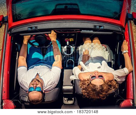 Happy couple travel by car. Woman and man having fun in red cabriolet. Summer vacation and travel concept. Top view