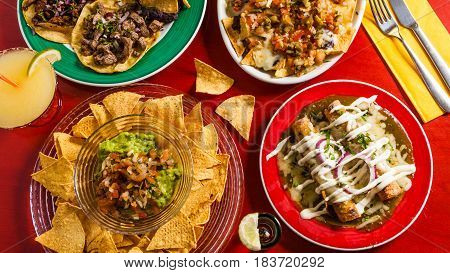 Mixed mexican food: Guacamole nachos fajita meat tacos. Top view. Tex-mex cuisine. Assorted appetizers. Cuisine of Mexico