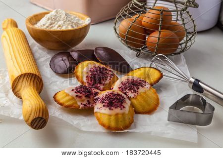 Making French butter cakes called Madeleines on a kitchen table.