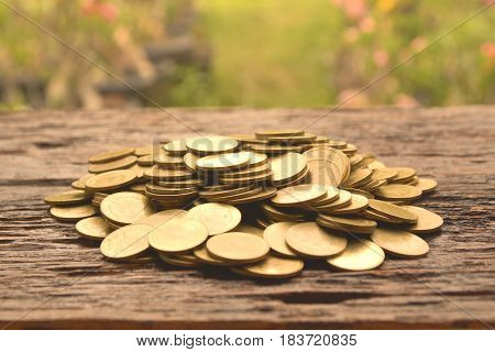 pile of gold coin on the wooden background financial and saving concept.