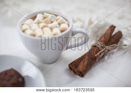 one white mug on a white background with marshmallow and candy