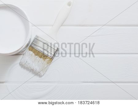 Bank paints and brush on a white wooden background