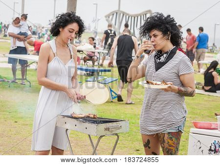 TEL AVIV, ISRAEL. May 6, 2014. Two young unknown Israeli women make barbecue on the Independence day of Israel in a public park. Israel Independence Day party stock image.