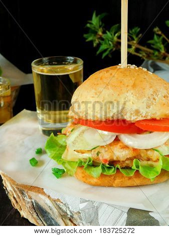 Layered club sandwich with a glass of a drink on a stump with a newspaper