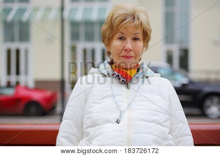 Elderly blonde woman in white jacket sits on bench outdoor, shallow dof