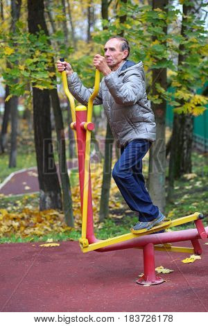 Elderly man is engaged on sport simulator in autumn park with fallen leaves