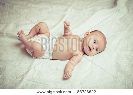 happy baby lying on white sheet and holding his legs