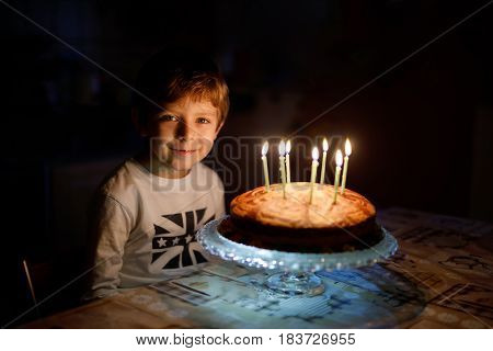 Adorable happy blond little kid boy celebrating his birthday. Child blowing seven candles on homemade baked cake, indoor. Birthday party for school children, family celebration of 7 years.