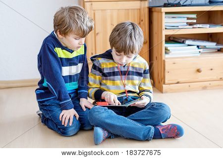 Two little kid boys reading a book at home. Older schoolboy reading for his brother, preschool sibling a fairytale or story. Family, children, education and leisure.