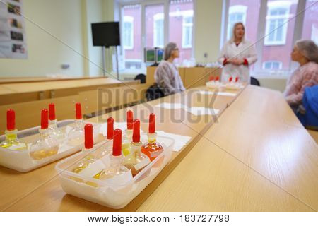 Test tubes with solutions in containers on table and three women speak out of focus in room