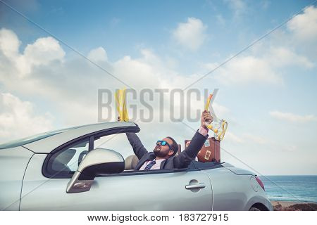Businessman Standing On A Beach Near Car