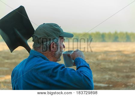 Senior farm worker contemplating field with coffee in morning