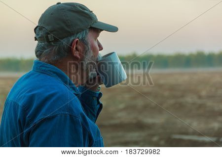 Senior farmer contemplating field with coffee in morning