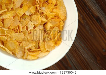 Tasty golden cornflakes in a white bowl on a wooden table. Top view flat lay
