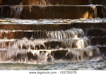 Small waterfall from pool with water flowing over short steps
