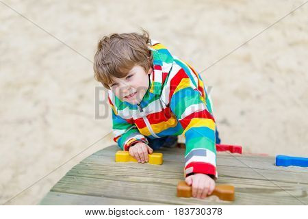 Happy blond kid boy having fun and climbing on outdoor playground. Funny joyful child smiling and making sports. Summer, spring and autumn leisure for active kids. Boy in colorful fashion clothes