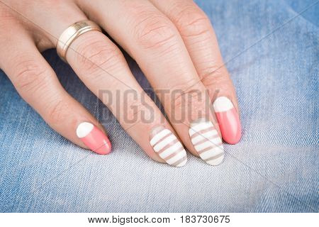 Beautiful female manicure close-up, on blue jeans