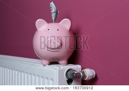 Piggy bank with money on pink background