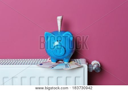 Cute blue piggy bank with money on pink background