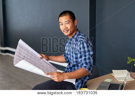 Portrait of a casually dressed young Asian architect smiling confidently while sitting on a desk in a modern office reading blueprints