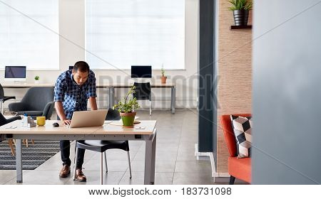 Young Asian designer focused on working on a laptop while leaning on his desk in a bright modern office