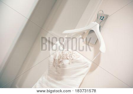 White dress of bride on hanger, symbol nubile, beautiful luxury cream wedding dress for bride