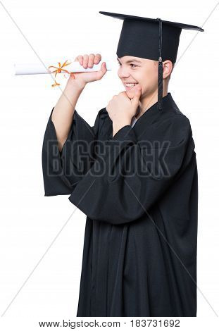 Portrait of a graduate teen boy student in a black graduation gown with hat, holding diploma - isolated on white background. Child back to school and educational concept.