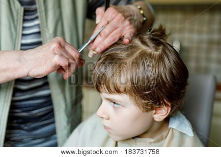 Beautiful kid boy with blond hairs getting his first haircut. Hands of hair stylist cutting curly hairs with scissors. Happy child sitting and waiting.