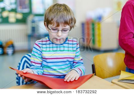 Little school kid boy with glasses playing with colorful paper and making geometric figures in mathematics class. child having fun with learning, building skills, education. Primary school and pupil.
