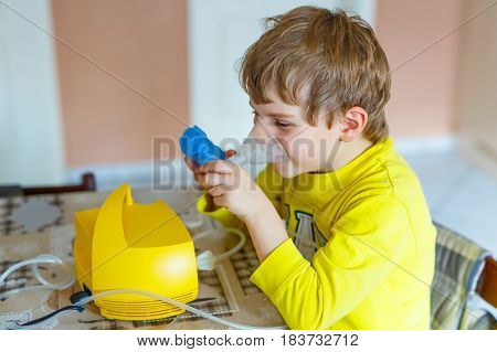 Cute boy making inhalation therapy by the mask of inhaler. Close up image of a little sick kid. Sad child with clear oxygen mask.