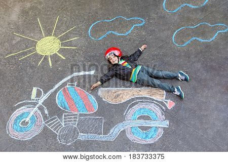 Happy kid boy in race helmet having fun with motorcycle picture drawing with colorful chalks. Children, lifestyle, fun concept. Creative leisture for kids