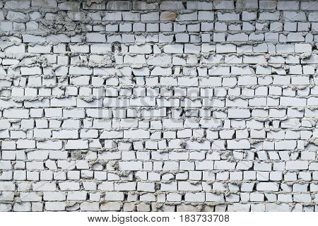 Brick wall white brick. Laying sloppy. Bricks of different sizes chipped. Cement mortar climbed out. On the wall there is a dirty spot.