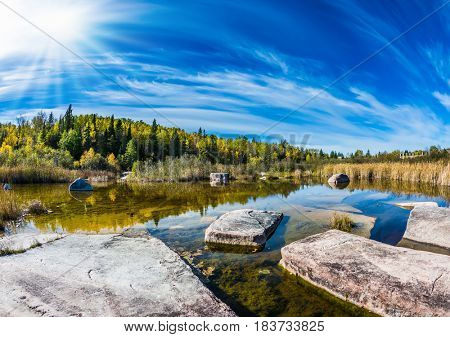 Huge flat stones in riiverbed of Winnipeg River. Old Pinawa Dam Park. Indian summer in Manitoba, Canada. The concept of recreational tourism