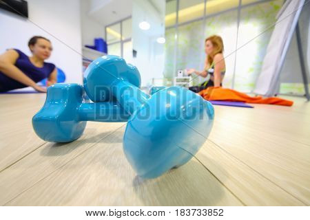 Two blue dumbbells are on floor, two women are in hall for fitness out of focus