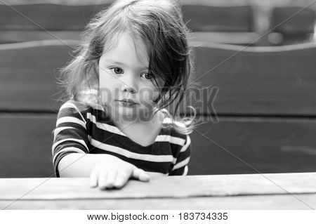 Close-up outdoor portrait of beautiful adorable toddler girl sitting by wooden table in outdoor cafe. Cute child with long hairs and in casual fashion clothes. In black-and-white